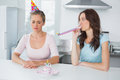 Woman cheering up her upset friend on her th birthday in the kitchen Royalty Free Stock Photography