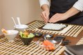 Woman chef filling japanese sushi rolls with rice Royalty Free Stock Photo