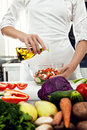 Woman chef professional female dressing salad with olive oil in a professional kitchen Stock Photo