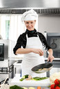 Woman chef professional female in a professional kitchen with a frying pan in hand Royalty Free Stock Images