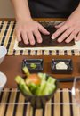 Woman chef ready to prepare japanese sushi rolls with principal ingredients in the foreground selective focus in nori seaweed Stock Photography