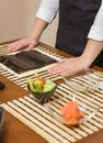 Woman chef ready to prepare japanese sushi rolls with principal ingredients in the foreground selective focus in nori seaweed Royalty Free Stock Image