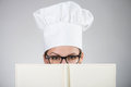 Woman in chef s hat looking over the cookbook closeup portrait of at camera on gray background Stock Image