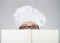 Woman in chef s hat looking over the cookbook closeup portrait of a on gray background Royalty Free Stock Photo