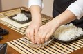 Woman chef wetting fingers to close sushi rolls japanese with rice on a nori seaweed sheet Stock Photography