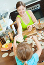 Woman with child cooking fish pelmeni (pelmeni), standing togeth