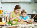 Woman with child cooking fish pelmeni (pelmeni), always together