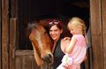 Woman and child with horse an attractive young caucasian women a blond little girl hugging her brown in the stable Royalty Free Stock Images