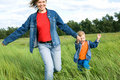 Woman and child run on field Stock Photos