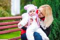 Woman with a child sitting on a park bench Stock Photo