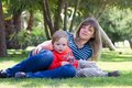 Woman with child a women a a boy on the green grass Stock Photography