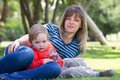 Woman with child a women a a boy on the green grass Stock Image