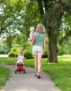 Woman with children strolling in park full length rear view of mid adult women Royalty Free Stock Photo