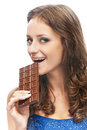Woman with chocolate bar young beautiful bites off slice from on white background Royalty Free Stock Image