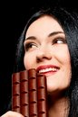 Woman with chocolate closeup portrait of beautiful young black hair holding a bar on black background Royalty Free Stock Photo