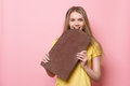 Woman with chocolate smiling. Cute girl holding and eating giant cocoa chocolate bar near pink wall