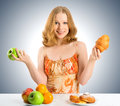 Woman choose between healthy and unhealthy food with a buns fruits Royalty Free Stock Photo