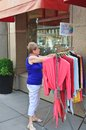 Woman chooses clothes on a hanger outside the shop on the street Royalty Free Stock Images