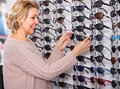 woman chooses sunglasses near the display Royalty Free Stock Photo
