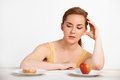 Woman Choosing Between Apple And Doughnut For Snack Royalty Free Stock Photo