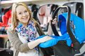Woman choosing child car seat for newborn baby in shop supermarket Stock Photos