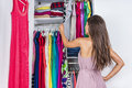 Woman choosing clothes to wear in clothing closet home her fashion outfit dressing room bedroom walk organized looking at hanging Stock Image