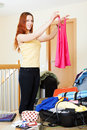 Woman choosing clothes for vacation at home Stock Photo