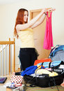 Woman choosing clothes for vacation red haired at home Royalty Free Stock Photo