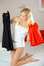 Woman choosing dresses at home Royalty Free Stock Photos