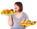 Woman choosing between fruit and hamburger. Royalty Free Stock Photo