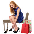 Woman choosing a new pair of shoes beautiful elegant young sitting on seat in store trying on stylish stilettos Stock Images