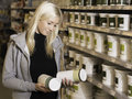 Woman choosing between products in hardware store deciding a diy Stock Image