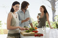 Woman chopping vegetables with friends communicating at kitchen counter portrait of smiling young women Royalty Free Stock Photo