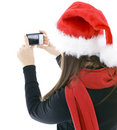 Woman in Christmas cap keeping digital camera Royalty Free Stock Images