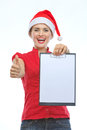 Woman in Christmas hat showing blank clipboard Royalty Free Stock Image