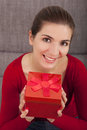 Woman with a christmas present beautiful and happy on the sofa holding Stock Images