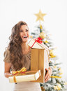 Woman with christmas present boxes in front of christmas tree Royalty Free Stock Photo