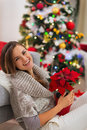 Woman with Christmas rose near Christmas tree Royalty Free Stock Images