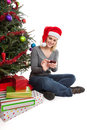 Woman christmas shopping online happy wearing santa hat for presents on a smart phone isolated on white Royalty Free Stock Photos