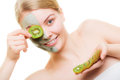 Woman in clay mask on face covering eye with kiwi