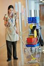 Woman cleaning building hall adult cleaner maid with mop and uniform corridor pass or floor of business Stock Photo