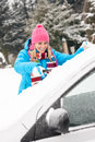 Woman cleaning car windshield of snow winter Royalty Free Stock Photos
