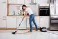 Woman Cleaning The Dust Floor Of The Kitchen Royalty Free Stock Photo