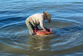 A woman cleaning fish on the sea in Cam Ranh bay, Vietnam Royalty Free Stock Photo