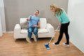 Woman cleaning floor while man on sofa Royalty Free Stock Photo