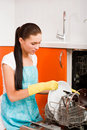 Woman cleaning kitchen using dish washing ma Stock Images