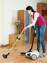 Woman cleaning with vacuum cleaner on parquet at home Stock Photo