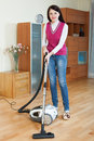 Woman cleaning with vacuum cleaner smiling brunette at home Stock Images