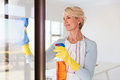 Woman cleaning window glass beautiful senior Royalty Free Stock Photography