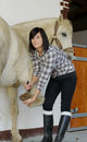 Woman cleans the horse x s hooves beautiful brunette young Stock Photos